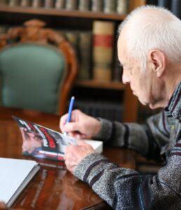 """Adam Macedoński składa dedykację na publikacji autobiograficznej """"Pod czerwoną okupacją"""" (fot. Lilianna Pochwalska)"""