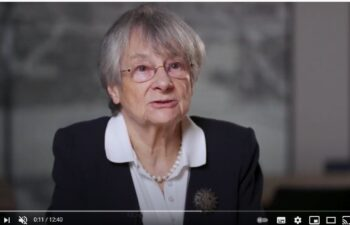 na fotografii dr Rita Mojkowska ubrana w ciemną garsonkę w trakcie prelekcji