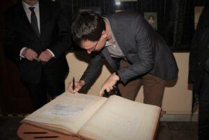 Tomasz Daros dokonuje wpisu do ksiegi pamiatakowej