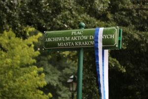 zielona tabliczka z napisem Plac Archiwum Aktów Dawnych Miasta Krakowa przepasana biało niebieską wstęgą