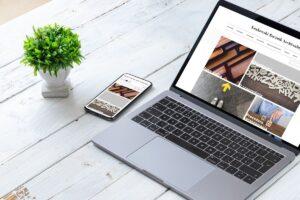 rustykalny biały blat na którym leży laptop z widokiem strony internetowej Krakowskiego Rocznika ARchiwalnego oraz smartphonu