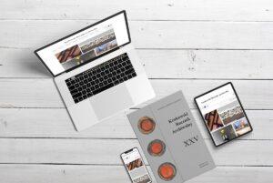 rustykalny blat na którym leży laptop z widokiem strony internetowej Krakowskiego Rocznika ARchiwalnego oraz smartphonu