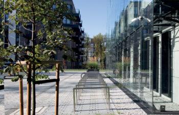widok na szklaną elewację nowej siedziby Archiwum, widoczna po lewej stronie zieleń na środku stojaki dla rowerów