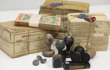 Kolorowa fotografia prezentacja tłoków pieczeniach i klocków drukarskich i plików banknotów zebranych i ułożonych obok siebie w celu prezentacji bogactwa zasobu