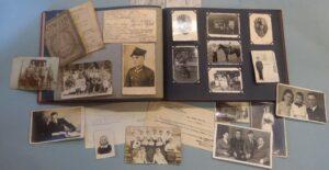 Kolorowa fotografia przedstawiająca album ze zdjęciami portretowymi i rodzinnymi z początku XX w., oraz luźne fotografie i dokumenty ułożone na niebeskim papierze.