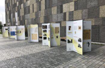 Plansze wystawy plenerowej ułożone wzdłuż fasady budynku