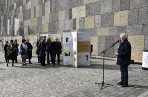 Marek Świca, Dyrektor Muzeum Fotografii w Krakowie przemawia do mikrofonu, po lewej zgromadzona publiczność stojąca obok plansz wystawy