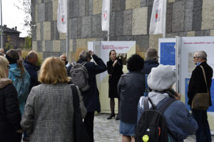 Barbara Zbroja, kurator wystawy, oprowadza po wystawie, na pierwszym planie zgromadzona publiczność
